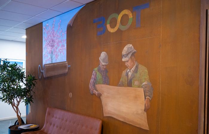 Op deze foto is een muurschildering in de entree van bureau Boot te zien waar twee mannen  een papieren bouwplan vast hebben