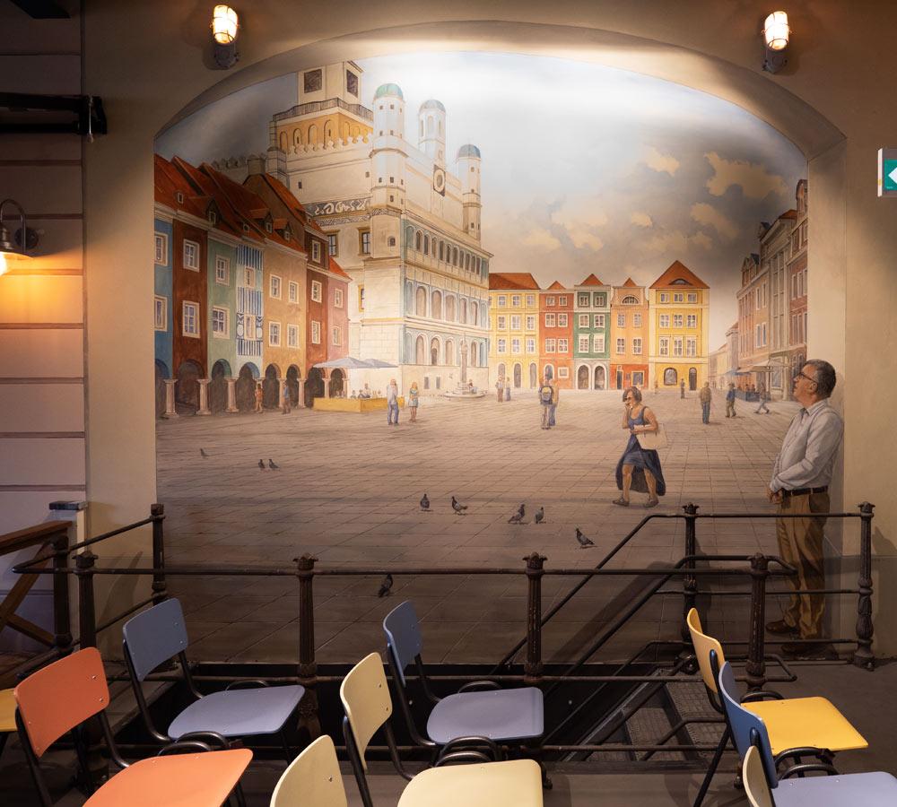 Je ziet hier een muurschildering met een plein, een man kijkt naar dit bijna lege plein. Er lopen wat mensen en je ziet enkele duiven.