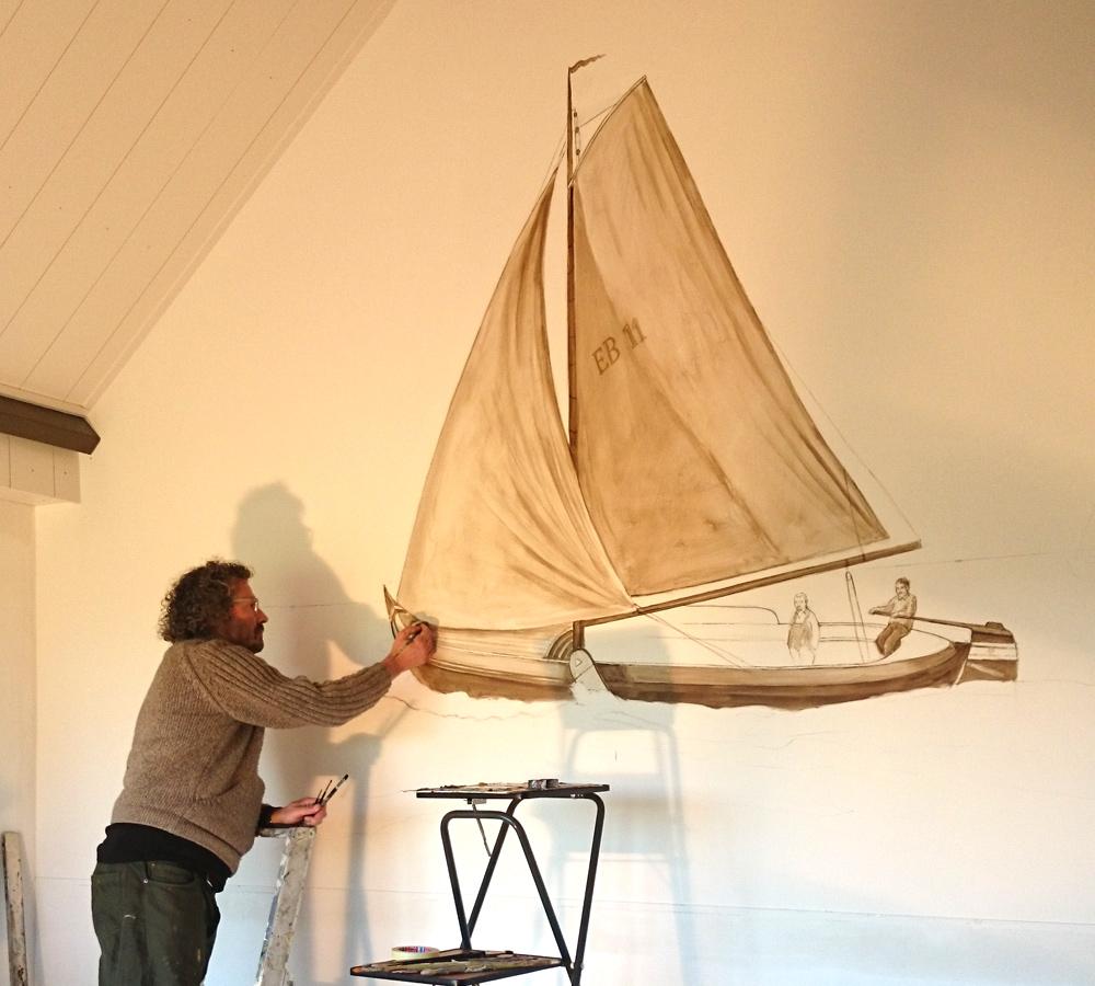 Op deze foto zie je Govert die een zeilboot aan het schilderen is
