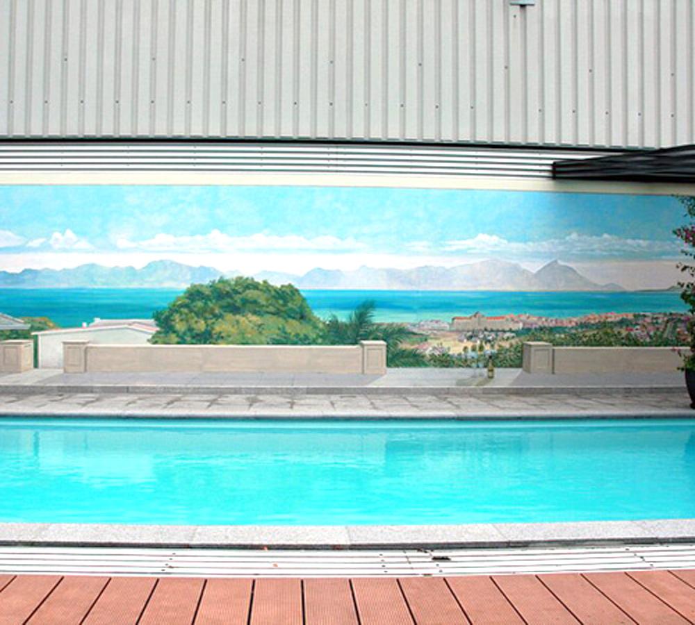 Te zien is een helderblauw zwembad met op de achtergrond een muurschildering waar de tafelberg in Zuid-Afrika te zien is